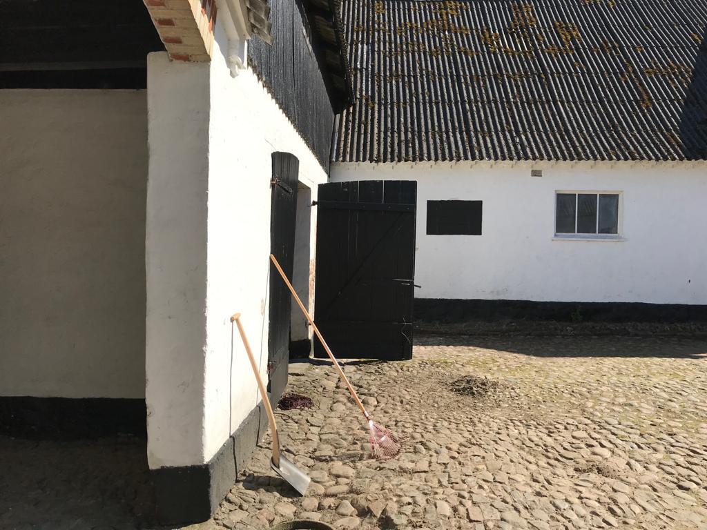 Gårdsplads med indgang i hjørnet ind til loen